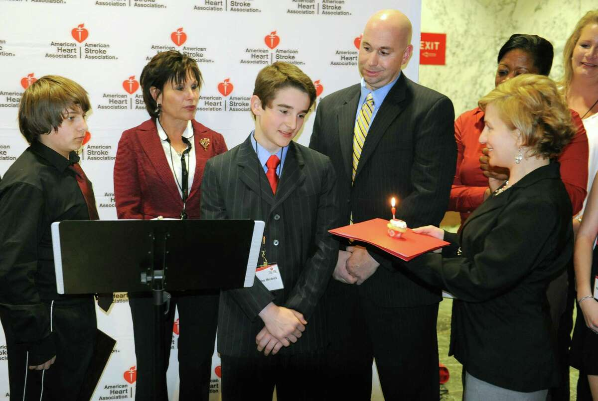 Meredith Cohn of the American Heart Association delivers a candlelit cupcake to Joey Mendrick of Colonie, middle, as he is joined by American Heart Association volunteers urging legislators to pass the CPR in Schools bill and create a generation of lifesavers outside the LOB on Tuesday, April 16, 2013 in Albany, N.Y. Joey, who exactly one year ago to the date of April 16, suffered commotio cordis when a baseball struck him in the chest and he was saved by Brian Curran, right, who performed CPR. Next to Joey is Casey Stashenko, left, of Colonie who perfomed CPR on his dad and Karen Acompora of Northport who lost her son Louis who was a lacrosse player. (Lori Van Buren / Times Union)