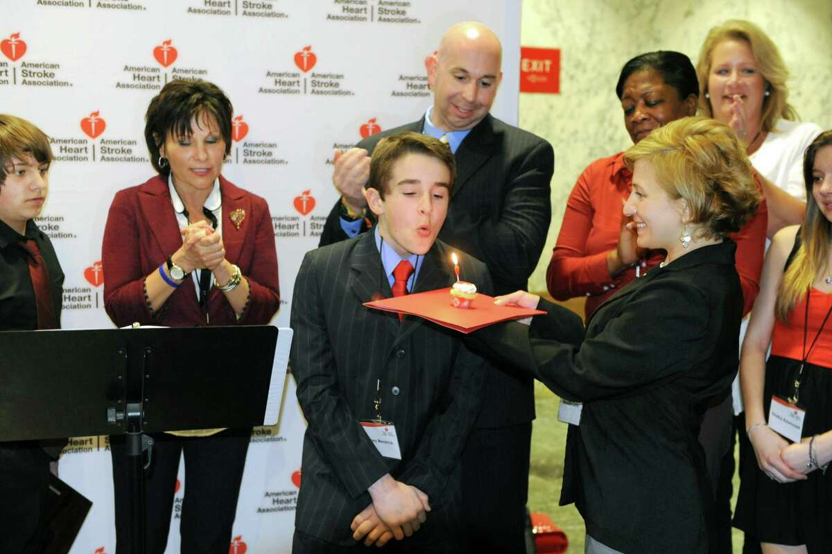 Meredith Cohn of the American Heart Association delivers a candlelit cupcake to Joey Mendrick of Colonie, middle, as he is joined by American Heart Association volunteers urging legislators to pass the CPR in Schools bill and create a generation of lifesavers outside the LOB on Tuesday, April 16, 2013 in Albany, N.Y. Joey, who exactly one year ago to the date of April 16, suffered commotio cordis when a baseball struck him in the chest and he was saved by Brian Curran, fourth from left, who performed CPR. Next to Joey is Casey Stashenko, left, of Colonie who perfomed CPR on his dad and Karen Acompora of Northport who lost her son Louis who was a lacrosse player. (Lori Van Buren / Times Union)