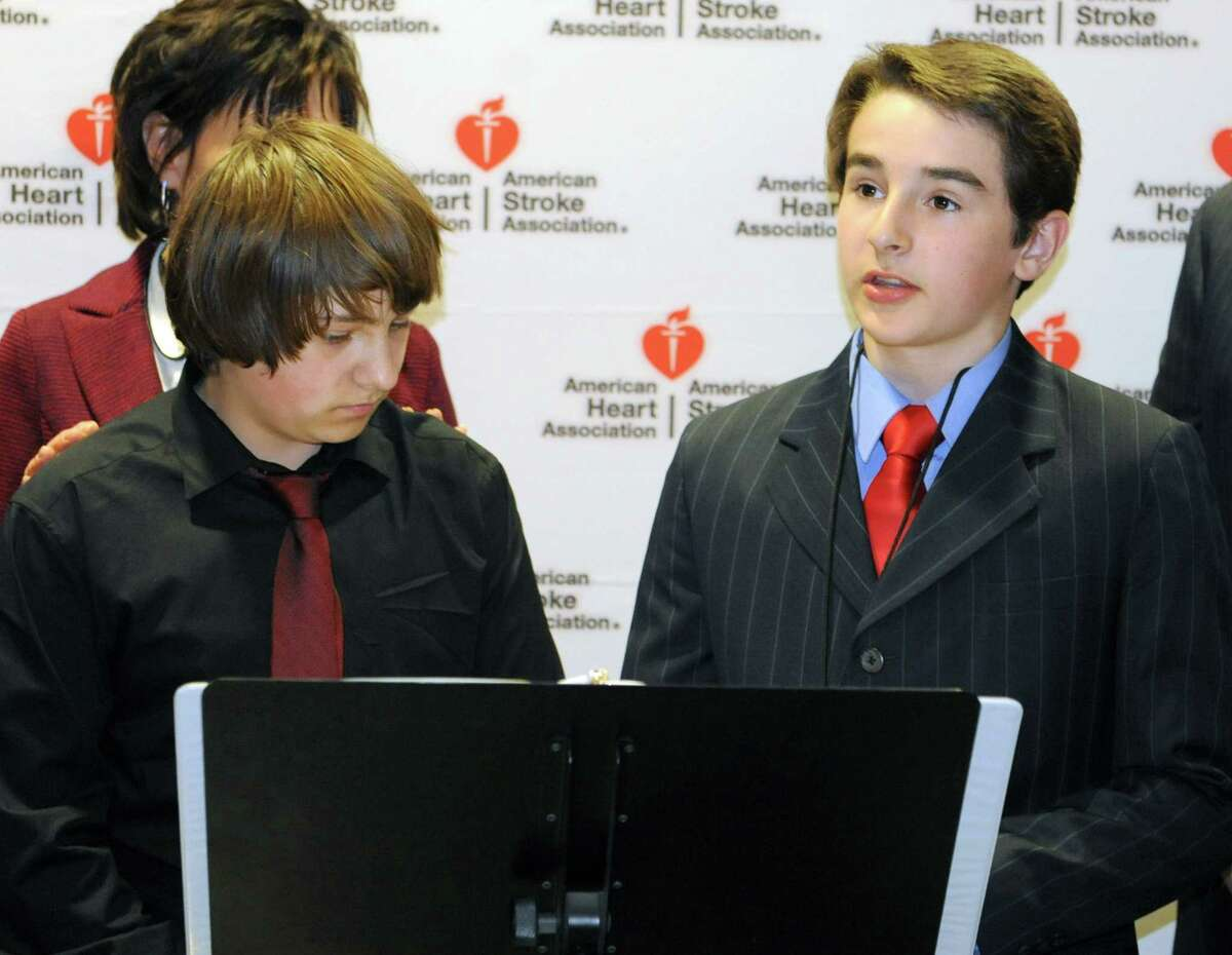 Joey Mendrick, 12, of Colonie, right, speaks as he is joined by American Heart Association volunteers urging legislators to pass the CPR in Schools bill and create a generation of lifesavers outside the LOB on Tuesday, April 16, 2013 in Albany, N.Y. Joey, who exactly one year ago to the date of April 16, suffered commotio cordis when a baseball struck him in the chest and he was saved by CPR. Next to Joey is Casey Stashenko, left, of Colonie who perfomed CPR on his dad and Karen Acompora of Northport who lost her son Louis who was a lacrosse player. (Lori Van Buren / Times Union)