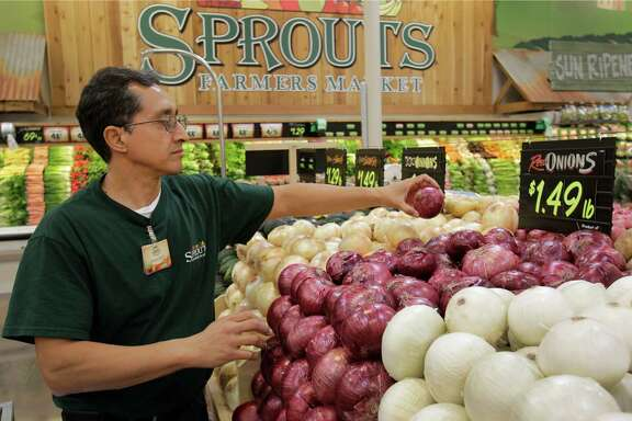 Assistant manager Francisco Siliezar stacks onions at the Sprouts Farmers Market at 22506 Tomball Parkway. Produce is a focus for the chain, says Steve Black, the company's chief information and marketing officer.