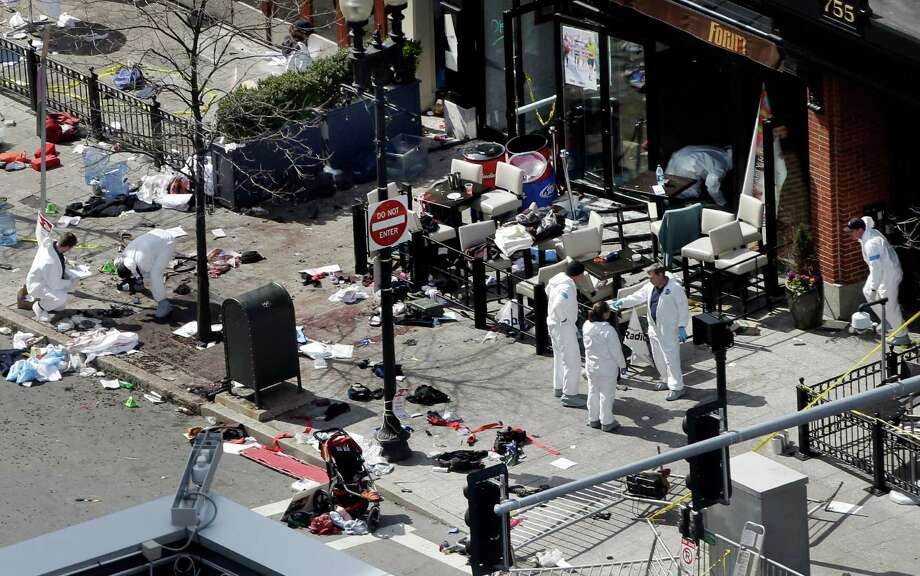 Investigators in haz-mat suits examine the scene of the second bombing on Boylston Street in Boston Tuesday, April 16, 2013 near the finish line of the 2013 Boston Marathon, a day after two blasts killed three and injured over 170 people. (AP Photo/Elise Amendola) Photo: Elise Amendola