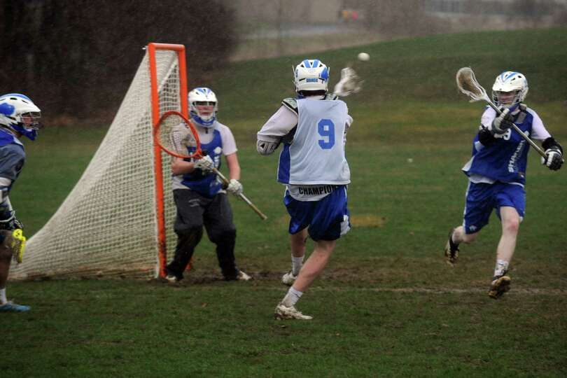 Player Tim Leahey takes a shot on goal during Shaker boy's varsity lacrosse practice on Tuesday Apri