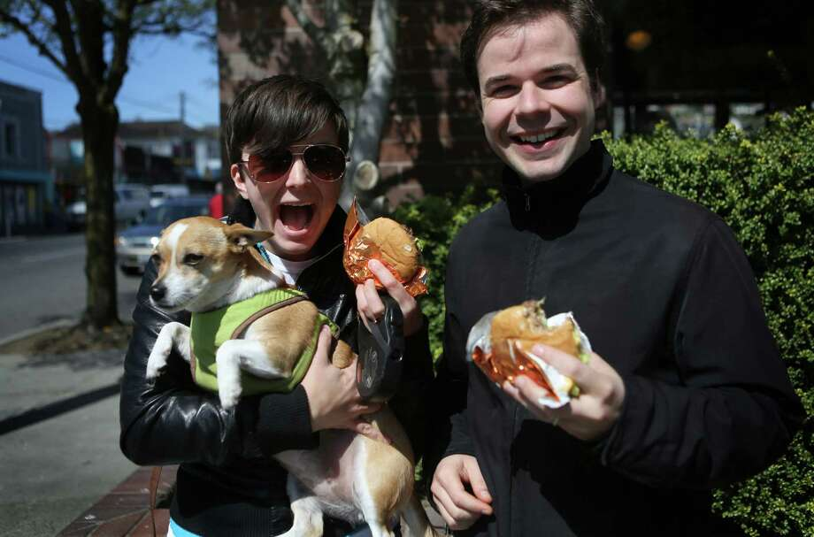 Shannon Erickson and Josh Aaseng enjoy their free burgers while holding onto Luna during a seattlepi.com promotion. Photo: JOSHUA TRUJILLO, SEATTLEPI.COM / SEATTLEPI.COM