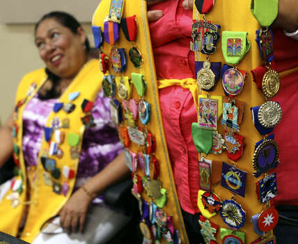 A sash made by Minerva Ray, whose face is outside the photographer's view, is decorated with about 50 Fiesta medals. Ray and Cynthia Rodriguez (left) were waiting for King Antonio and other Fiesta dignitaries, hoping to add to their medal collections. Click through for a look back at some of last year's Fiesta medals ...