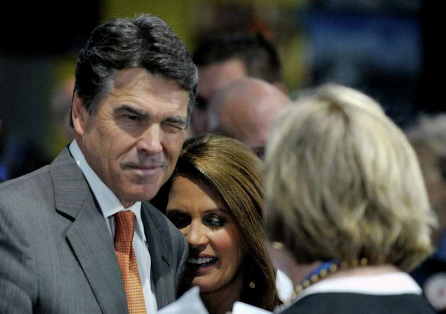 "Former Republican party presidential candidate Governor Rick Perry jokes with an activist during a pro-life event called ""Treasure Life"" at the Tampa Aquarium in Tampa, Florida on August 28, 2012. The Republican National Coalition for Life and FRC Action's event, ""Treasure Life,"" honored the pro-life contributions of the former Republican party presidential candidates Sen. Rick Santorum, Rep. Michele Bachmann and Gov. Rick Perry for their advocacy for every stage of life, from conception to natural death. Photo: MLADEN ANTONOV, AFP/Getty Images / AFP"