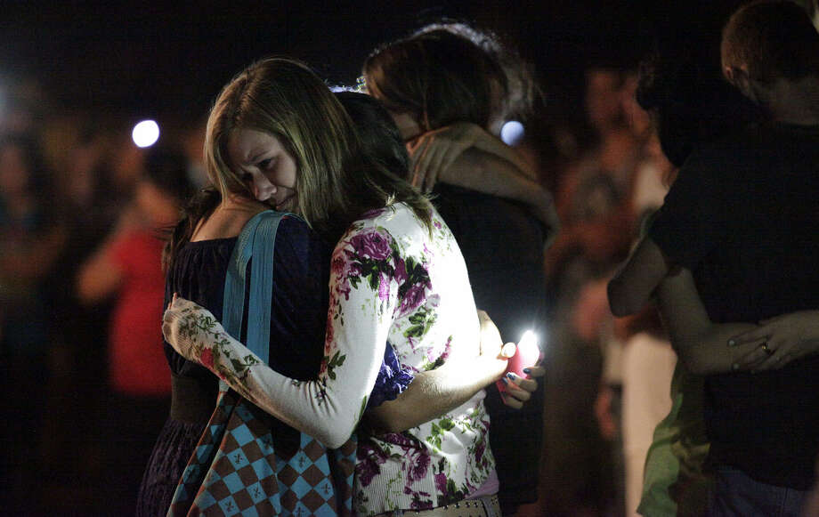 Kayla Morelli (right) is comforted by friend Angie Roberson as mourners gather for a candlelight vigil for the Koontz family.  Photo: Kin Man Hui, San Antonio Express-News