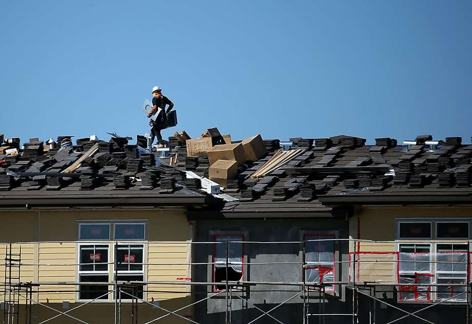 SAN MATEO, CA - APRIL 16:  A worker carries materials on the roof of housing development under construction on April 16, 2013 in San Mateo, California.  The Commerce Department reported that new home construction was up 7 percent in March from February, the biggest gain since June 2008. A surge of apartment construction led the monthly gain.   (Photo by Justin Sullivan/Getty Images) Photo: Justin Sullivan, Getty Images
