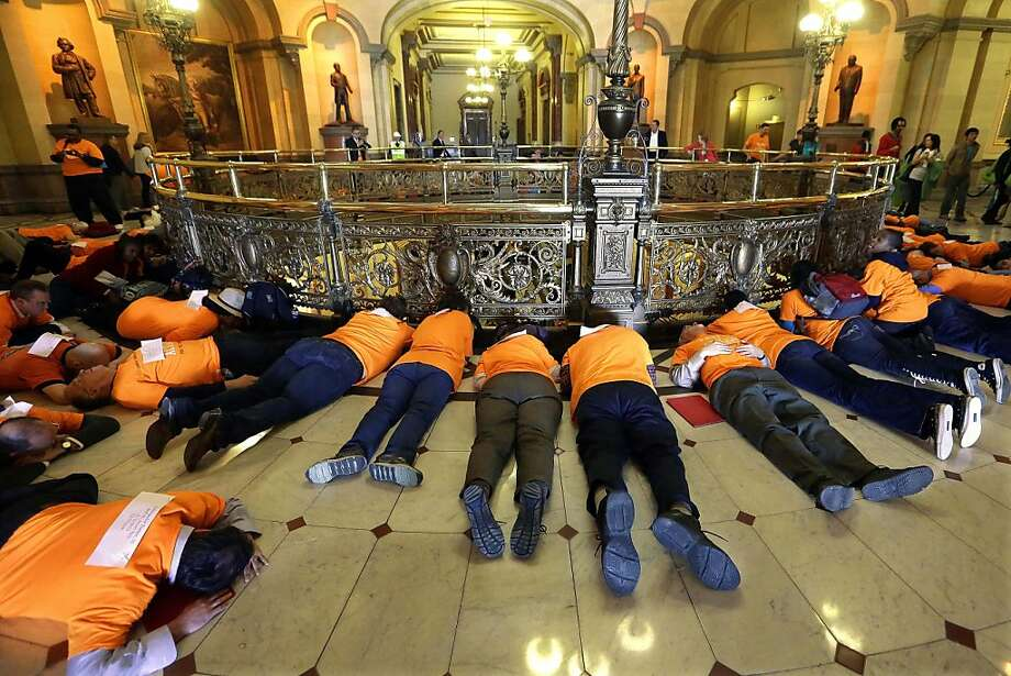 "Members of the Community Renewal Society from Chicago participate in a ""die-in"" protest to stop gun violence and support legislation to stop illegal gun trafficking and stronger laws for gun registration, in front of Illinois Gov. Pat Quinn's office at the Illinois State Capitol Tuesday, April 16, 2013, in Springfield, Ill. Each member is wearing the name of someone who has been killed by gun violence. (AP Photo/Seth Perlman) Photo: Seth Perlman, Associated Press"