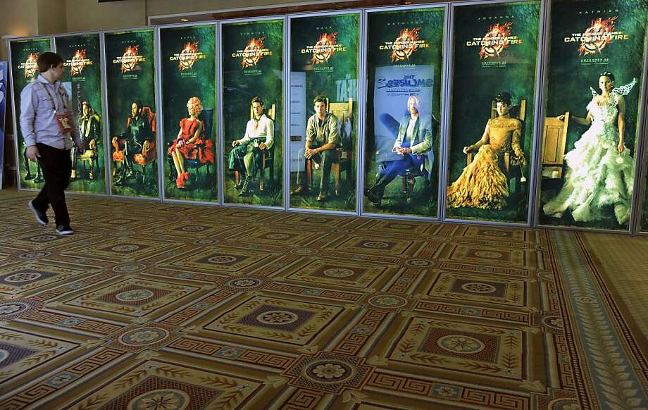 """A CinemaCon attendee walks past a bank of posters for the upcoming film """"The Hunger Games: Catching Fire,"""" during CinemaCon 2013 at Caesars Palace on Tuesday, April 16, 2013 in Las Vegas. (Photo by Chris Pizzello/Invision/AP) Photo: Chris Pizzello, Associated Press"""