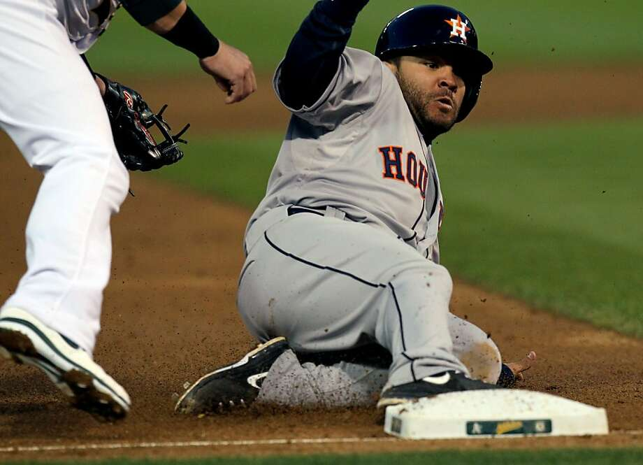 Houston Astros Jose Altuve slides safely into 3rd base ahead of the Oakland Athletics throw during their MLB baseball game Tuesday, April 16, 2013 in Oakland, Calif. Photo: Lance Iversen, The Chronicle