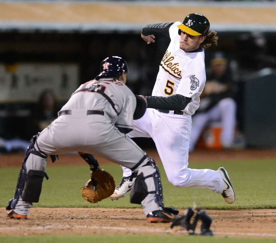 Jason Castro (15) left, gets ready to tag Athletics outfielder John Jaso (5) out at home plate in the fifth inning.