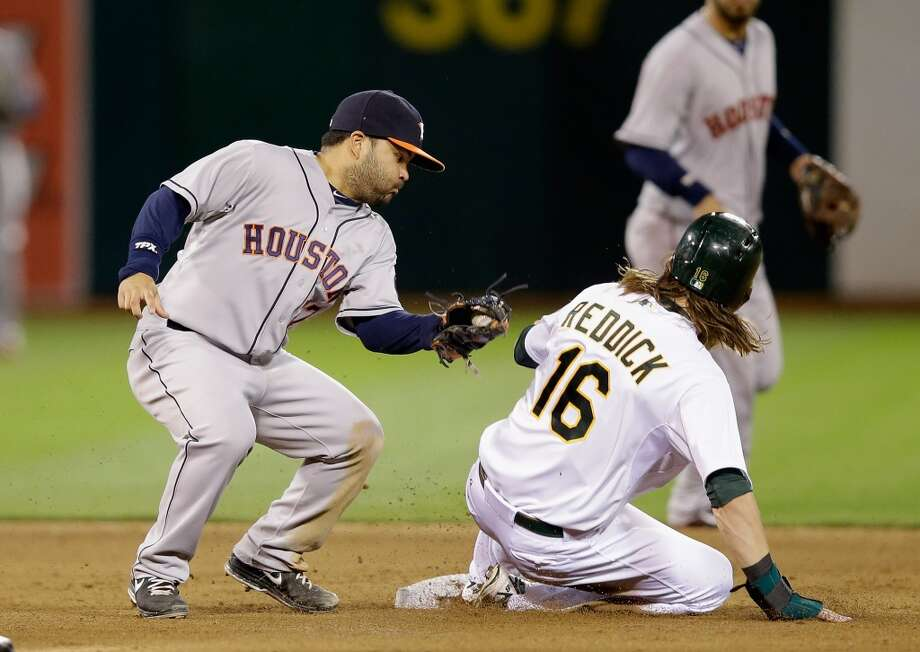 Josh Reddick #16 of the Athletics slides safely past the tag of Jose Altuve #27.