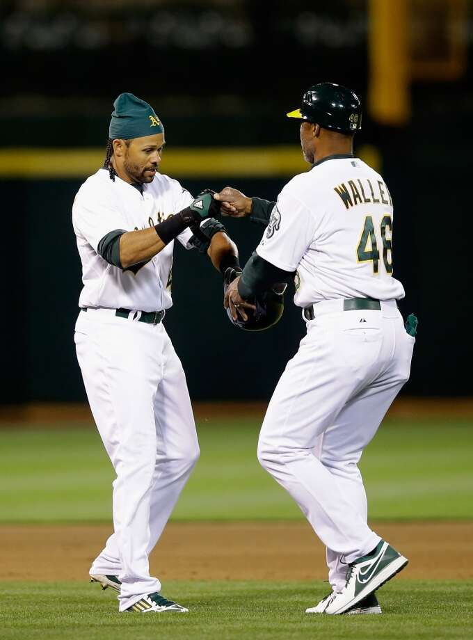 Coco Crisp #4 is congratulated by first base coach Tye Waller #46 after Crisp hit a triple that scored Eric Sogard #28 in the fifth inning.