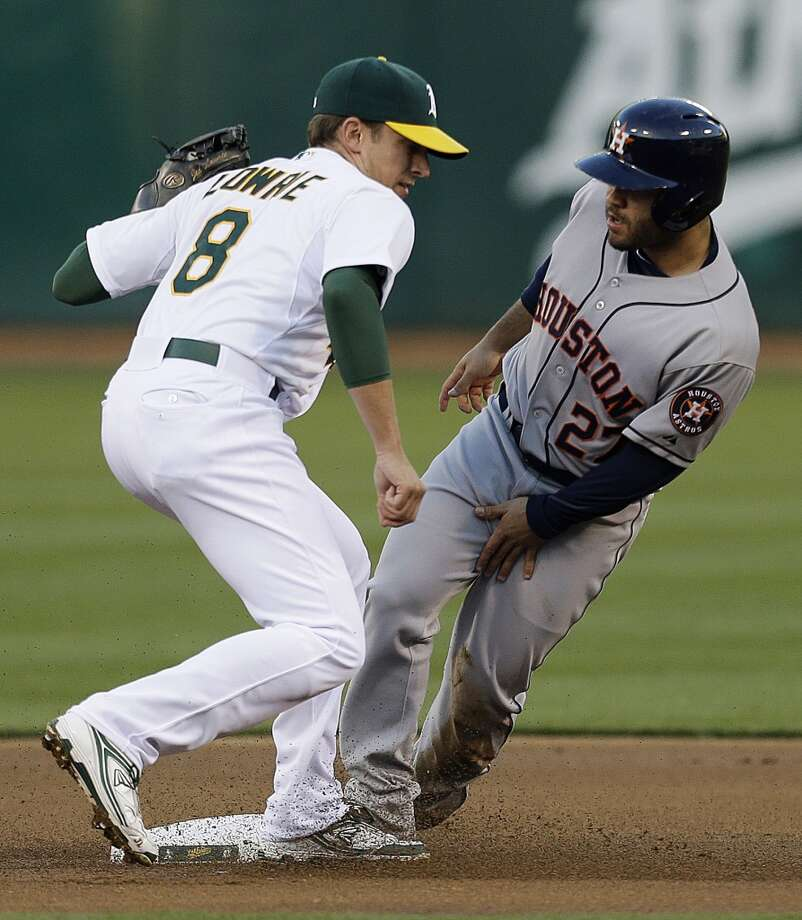 Jose Altuve, right, is tagged out by Athletics shortstop Jed Lowrie on a first-inning attempted steal. Photo: Ben Margot, Associated Press