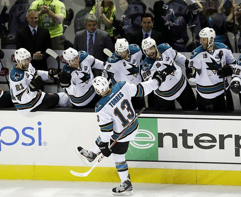 Raffi Torres heads down the reception line after scoring the game-winner for San Jose in a shootout. Photo: Marcio Jose Sanchez, Associated Press
