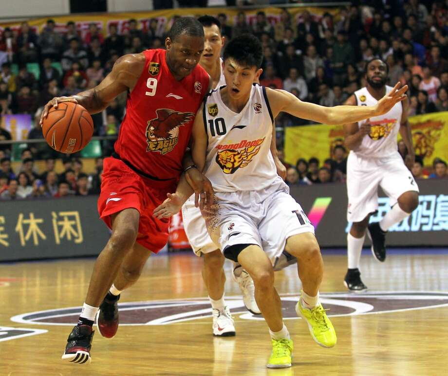 Liu Xiaoyu of Guangdong Southern Tigers defends against Tracy McGrady of Qingdao Eagles during the 34th round of the CBA 12/13 game at Dongguan Stadium on Feb. 17, 2013 in Dongguan, China.