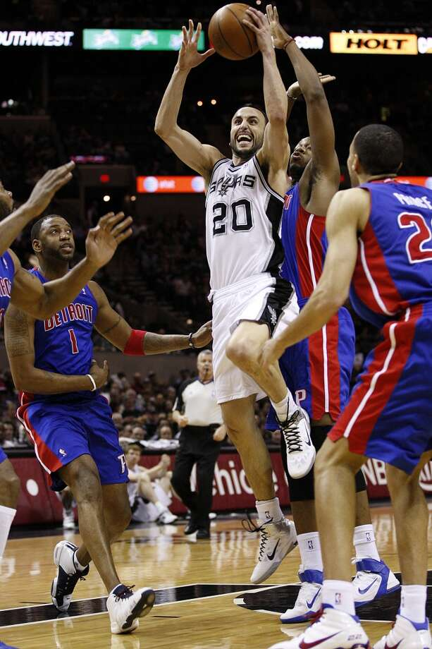 The Spurs\' Manu Ginobili drives through the Detroit Pistons\' Tracy McGrady (left) and Greg Monroe in the first half at the AT&T Center, on March 9, 2011.