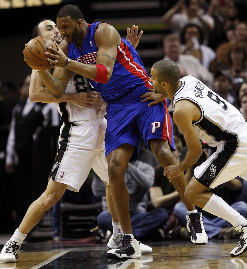 The Spurs\' Manu Ginobili (left) and Tony Parker tie up the Detroit Pistons\' Tracy McGrady in the first half at the AT&T Center, on March 9, 2011.