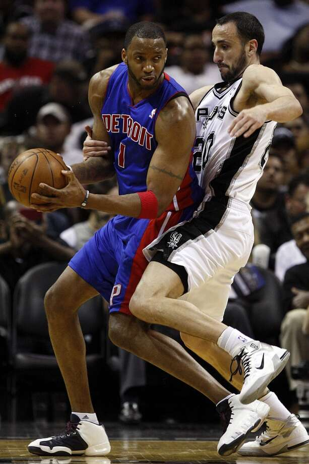 The Spurs\' Manu Ginobili tries to draw a foul from the Detroit Pistons\' Tracy McGrady in the second half at the AT&T Center, on March 9, 2011. The Spurs won 111-104.