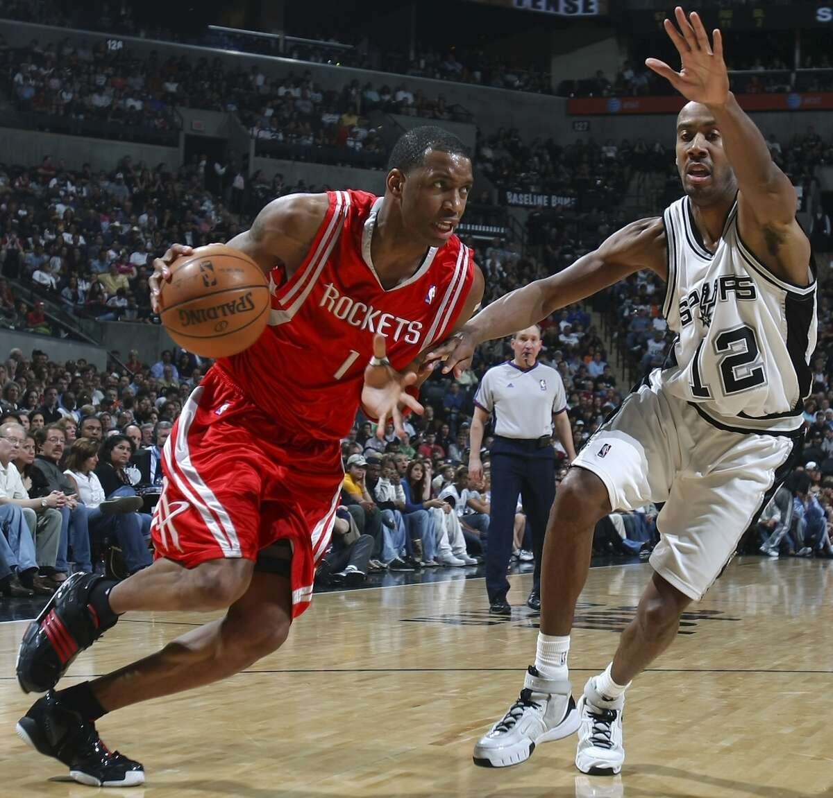 The Houston Rockets\' Tracy McGrady looks for room around the Spurs\' Bruce Bowen during the first half on March 30, 2008, at the AT&T Center.