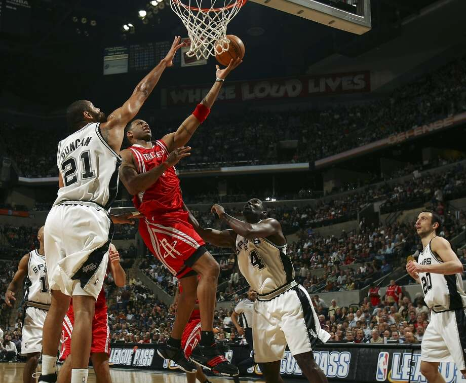 The Houston Rockets\' Tracy McGrady shoots between the Spurs\' Tim Duncan and Michael Finley, as Manu Ginobili looks on during the first half on March 30, 2008, at the AT&T Center.