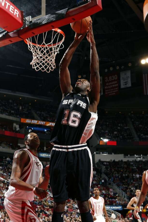 The Spurs\' Francisco Elson shoots the ball over the Houston Rockets\' Tracy McGrady on March 3, 2007 in Houston.