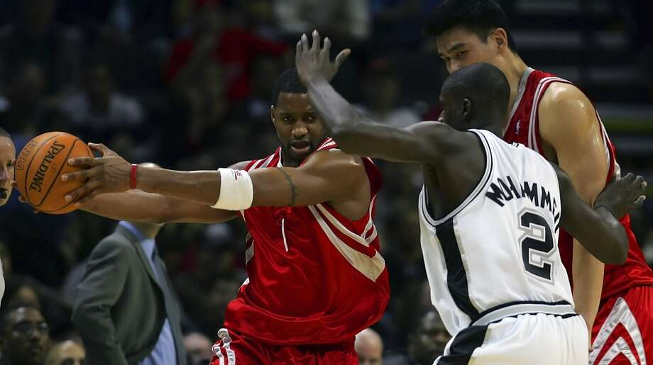 The Houston Rockets\' Tracy McGrady holds the ball away from the Spurs\' Nazr Mohammed as he moves around a pick by teammate Yao Ming in the first half on Nov. 17, 2005, at the SBC Center.