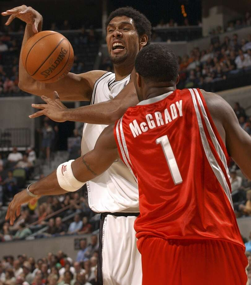 The Spurs\' Tim Duncan loses the ball as he is fouled by the Houston Rockets\' Tracy McGrady on Oct. 15, 2005, at the SBC Center.