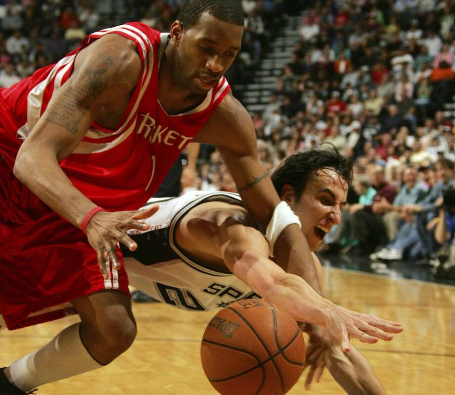 The Spurs\' Manu Ginobili steals the ball away from the Houston Rockets\' Tracy McGrady during the second half at the SBC Center on March 27, 2005.