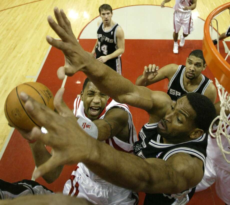 The Spurs\' Robert Horry (right) defends as the Houston Rockets\' Tracy McGrady (center) goes up for a shot during the first quarter on Jan. 15, 2005, in Houston.
