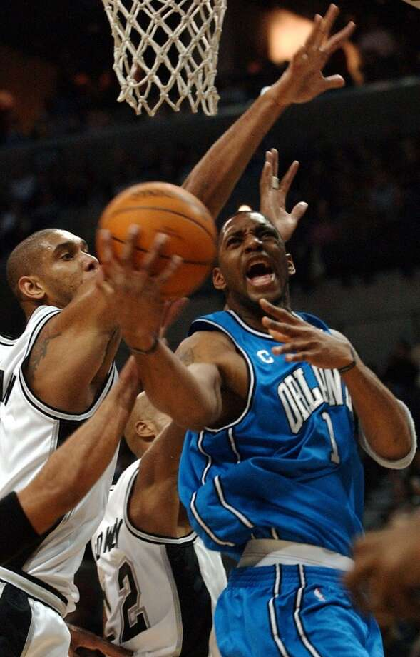 Orlando Magic guard Tracy McGrady (1), is fouled as the Spurs\' Tony Parker reaches in, and is surrounded by the Spurs\' Tim Duncan (21) and Bruce Bowen (12) during the first half on Dec 26, 2003, in San Antonio.