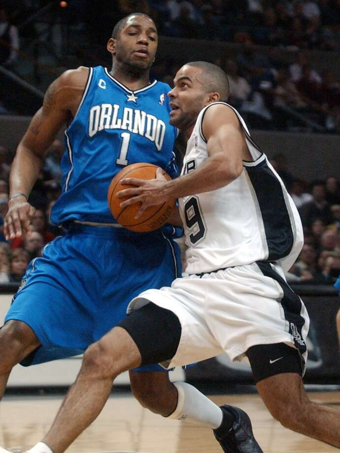 The Spurs\' Tony Parker slips under the Orlando Magic\'s Tracy McGrady for a layup in the first half at the SBC Center on Dec. 26, 2003.