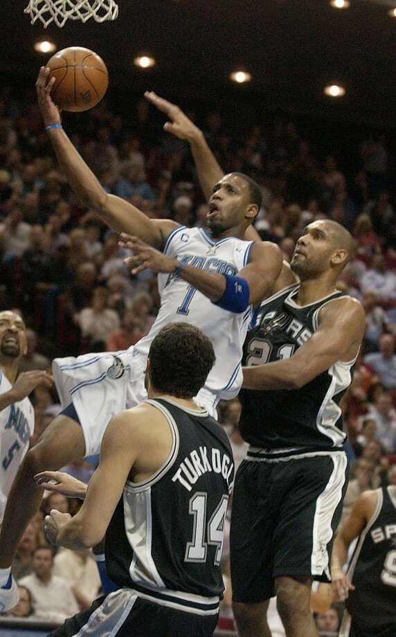 The Orlando Magic guard Tracy McGrady (1) goes for the basket against the Spurs\' Tim Duncan and Hedo Türkoğlu (14) during the first half in Orlando, Fla., on Dec. 5, 2003.