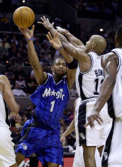 Orlando Magic guard Tracy McGrady (1) is defended by Spurs forward Bruce Bowen (12) during the third