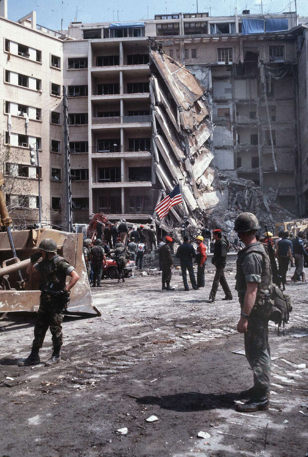 American Marines stand a stunned guard as rescuers examine the wreckage after the suicide truck bombing of the American embassy that killed 63 people including 17 Americans among them CIA station chief Robert Ames, Beirut, April 18, 1983. The US Marines were there as part of the failed Multinational Force peacekeeping intervention in the Lebanese Civil War. Photo: Francoise De Mulder, Roger Viollet/Getty Images / Francoise De Mulder/Roger Viollet