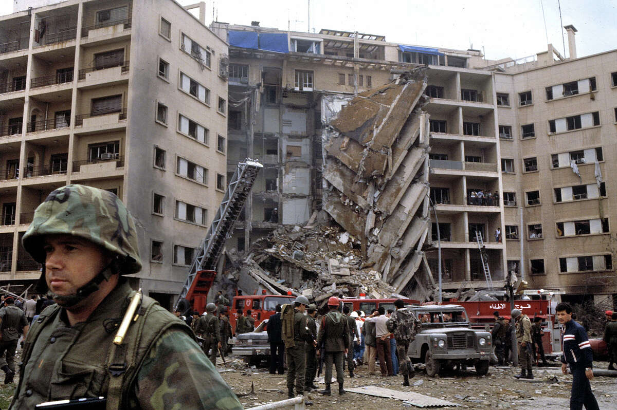 An American Marine Second Lieutenant stands with his back to rescue workers swarming the ruins of the American embassy after a suicide bomber attacked killing 63, including 17 Americans among them CIA station chief Robert Ames, Beirut, April 18, 1983. The US Marines were there as part of the failed Multinational Force peacekeeping intervention in the Lebanese Civil War.