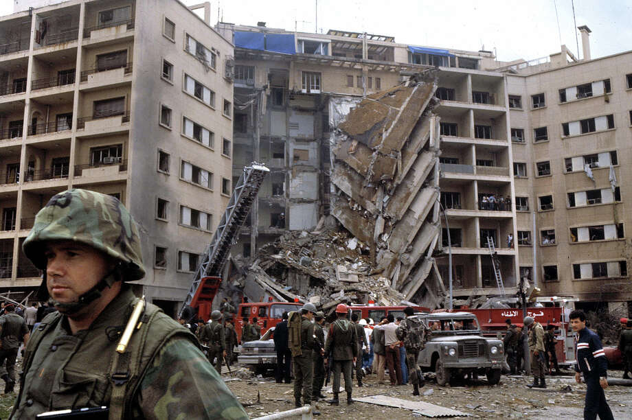 An American Marine Second Lieutenant stands with his back to rescue workers swarming the ruins of the American embassy after a suicide bomber attacked killing 63, including 17 Americans among them CIA station chief Robert Ames, Beirut, April 18, 1983. The US Marines were there as part of the failed Multinational Force peacekeeping intervention in the Lebanese Civil War. Photo: Francoise De Mulder, Roger Viollet/Getty Images / Francoise De Mulder/Roger Viollet