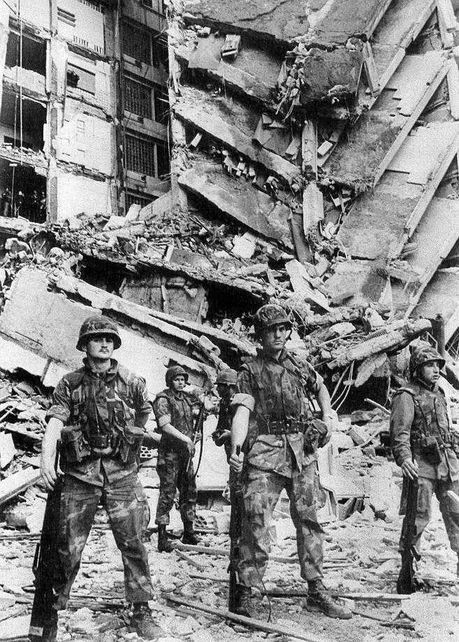 A group of U.S. Marines stand guard 18 April 1983 in front of the destroyed section of the U.S. embassy in Beirut.  A bomb partially destroyed the building killing and injuring scores of people. Photo: -, AFP/Getty Images / 2010 AFP