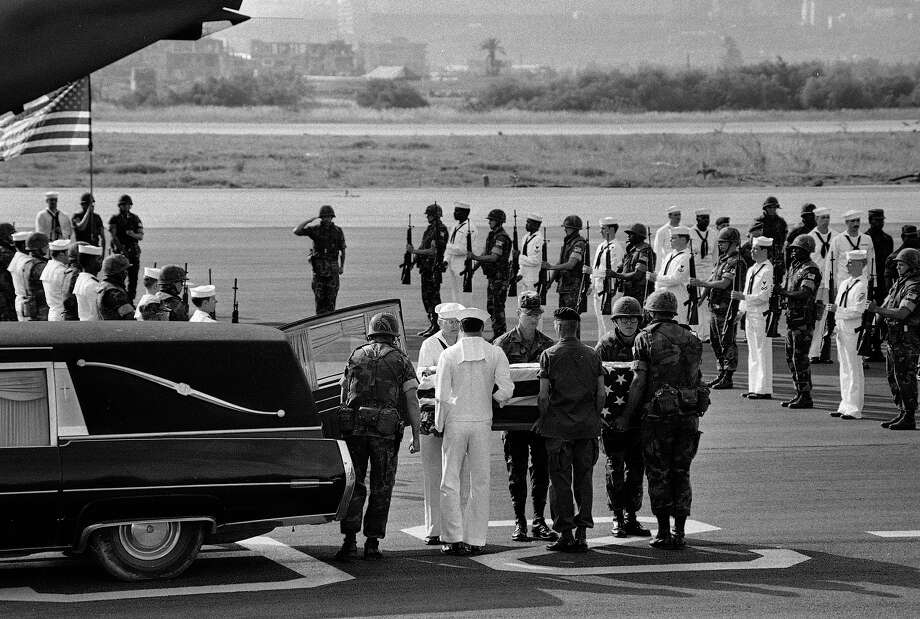 U.S. Marine and Navy pallbearers remove the coffin of one of the American staffers killed in the U.S. Embassy bomb blast in Beirut, from a hearse, April 23, 1983.  A Marine and Navy honor guard stands at attention as the bodies were then loaded on a C-141 transport plane bound for Washington.  Color guard and tail of plane are seen in the background. Photo: Zuheir Saade, ASSOCIATED PRESS / AP1983