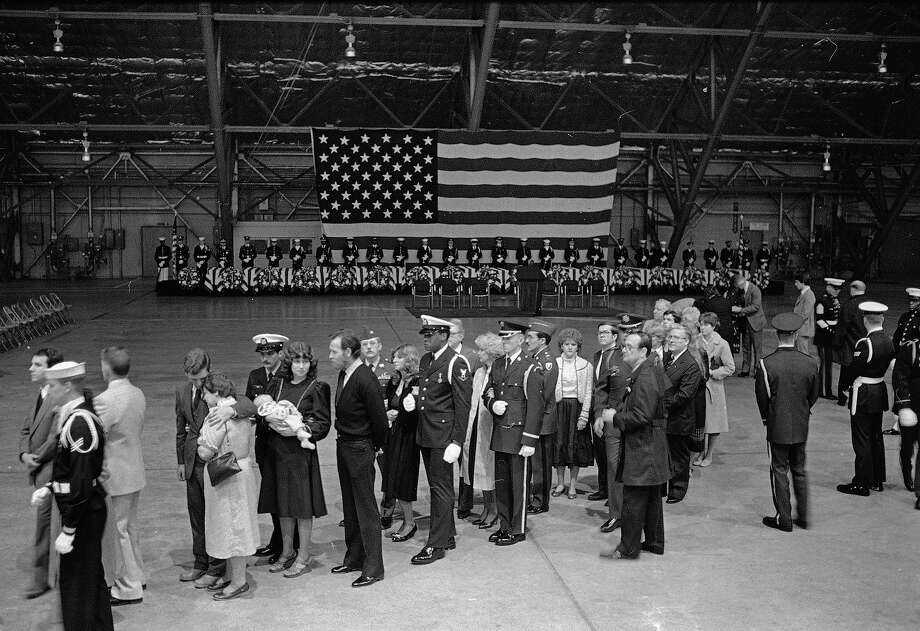 Family members of the Americans killed in the bombing of the American Embassy in Beirut line up after a ceremony at Andrews Air Force Base in Maryland, April 23, 1983.  The sixteen caskets that were flown home today are lined up at rear. Photo: Ed Reinke, ASSOCIATED PRESS / AP1983