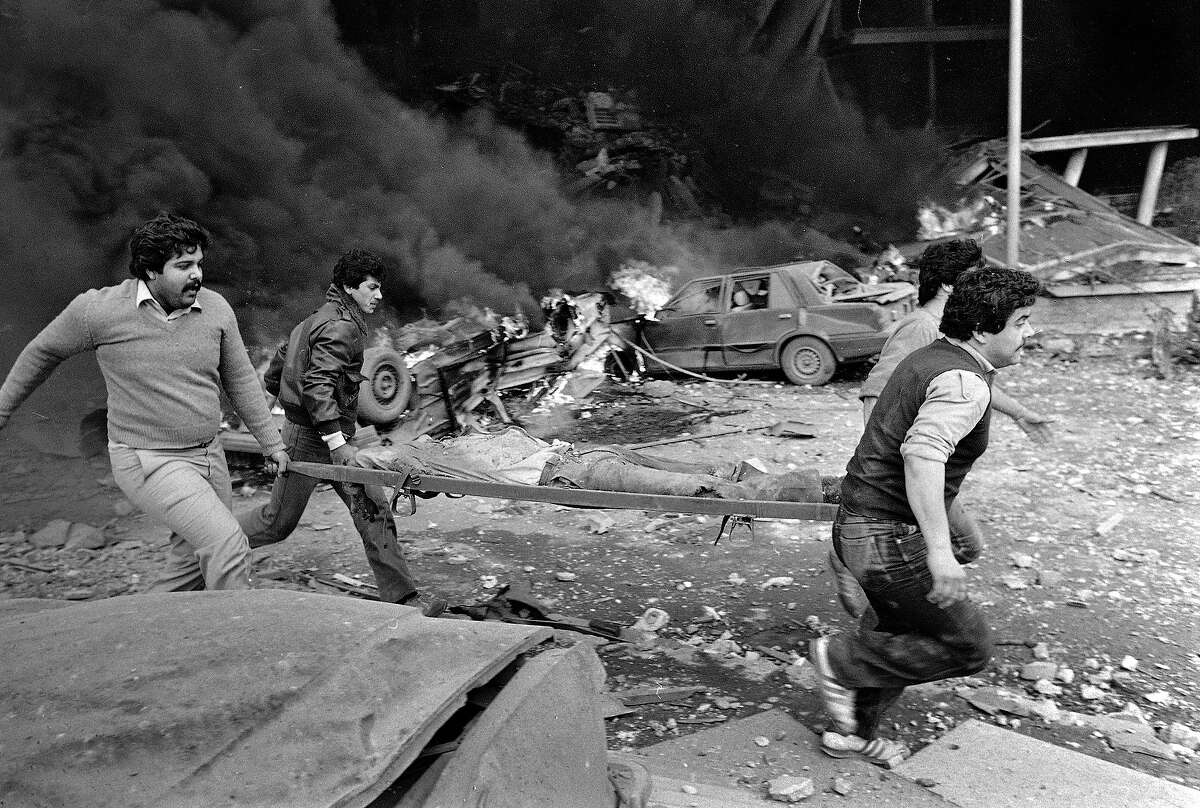 Rescue workers run as they carry a stretcher with a dead body on it, after a bomb blast collapsed the entire front of the American Embassy in West Beirut, April 18, 1983. They dug the body out of the rubble shortly after the explosion. A car burns in the background.