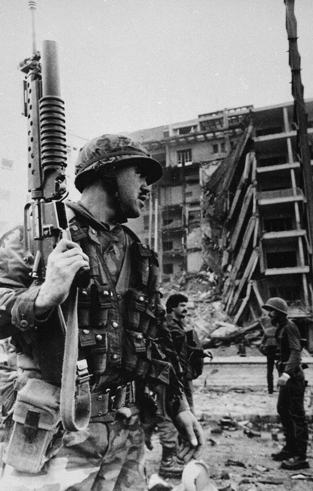 A U.S. Marine, armed with an automatic rifle/grenade launcher, stands guard outside the American Embassy after a huge bomb ripped throughout the building, collapsing the entire front section of the seven-story building, April 18, 1983, in Beirut, Lebanon.