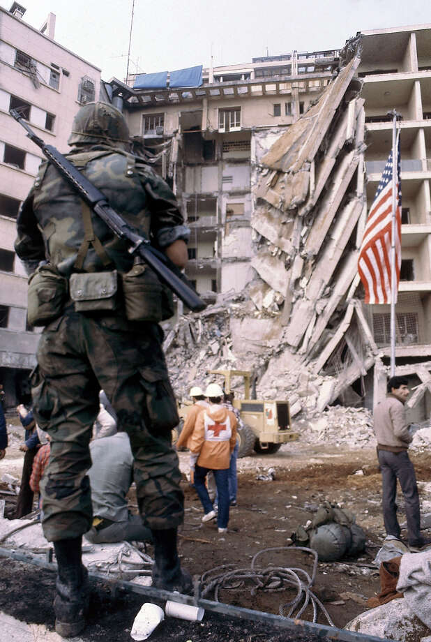 A U.S. Marine stands guard as rescue workers search the rubble of the U.S. Embassy in Beirut  for bodies.   Rescue workers search the collapsed front of the building after the terrorist bombing on April 18, 1983. Photo: Bill Foley, ASSOCIATED PRESS / AP1983