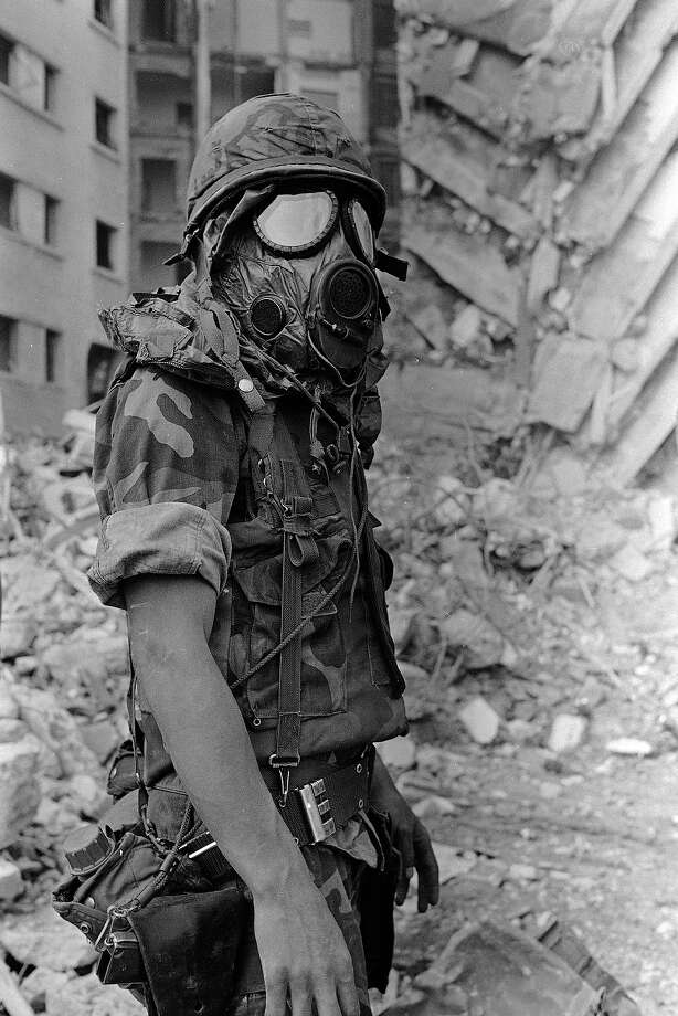 A U.S. Marine wears a gas mask after rescue workers using a backhoe broke open a stock of tear gas that had been stored in the Embassy, April 19, 1983.  Tear gas drifted up through the rubble, causing rescue workers and Marines to cough and sneeze.  The Embassy, seen in the background, was severely damaged in a bomb blast yesterday. Photo: Bill Foley, ASSOCIATED PRESS / AP1983