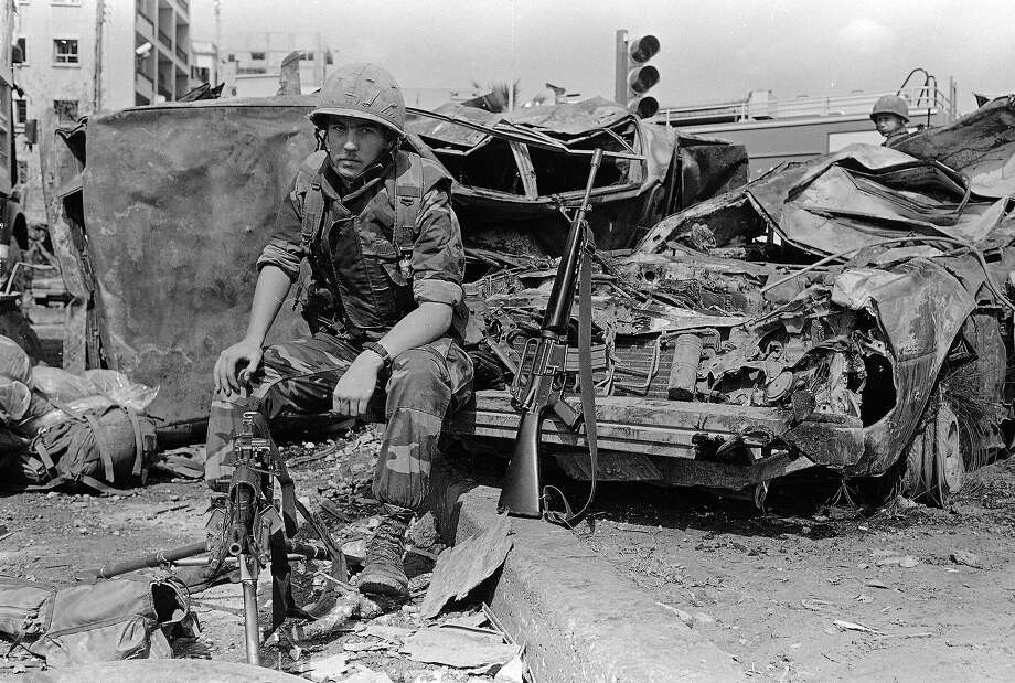 A U.S. Marine sits on the bumper of a car that was destroyed when a huge bomb explosion wrecked the American Embassy in West Beirut, April 19, 1983, where he is on guard duty across the street from the Embassy. Photo: Bill Foley, ASSOCIATED PRESS / AP1983