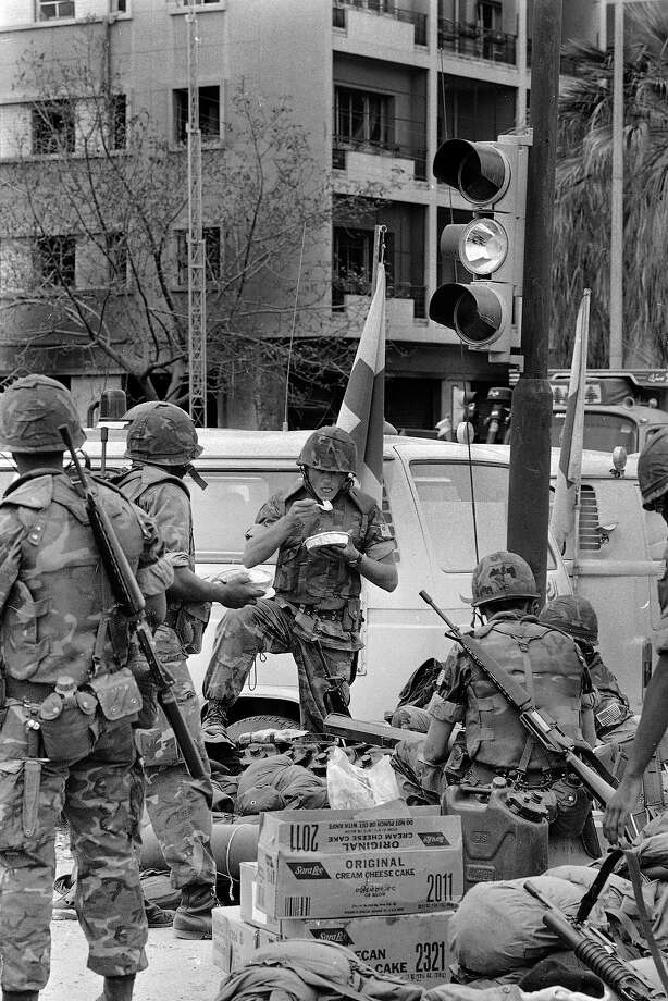 U.S. Marines on guard duty near the wreckage of the American Embassy in West Beirut,  take time out for lunch, April 20, 1983, two days after the building was destroyed in a bomb attack. Photo: Paola Crociani, ASSOCIATED PRESS / AP1983