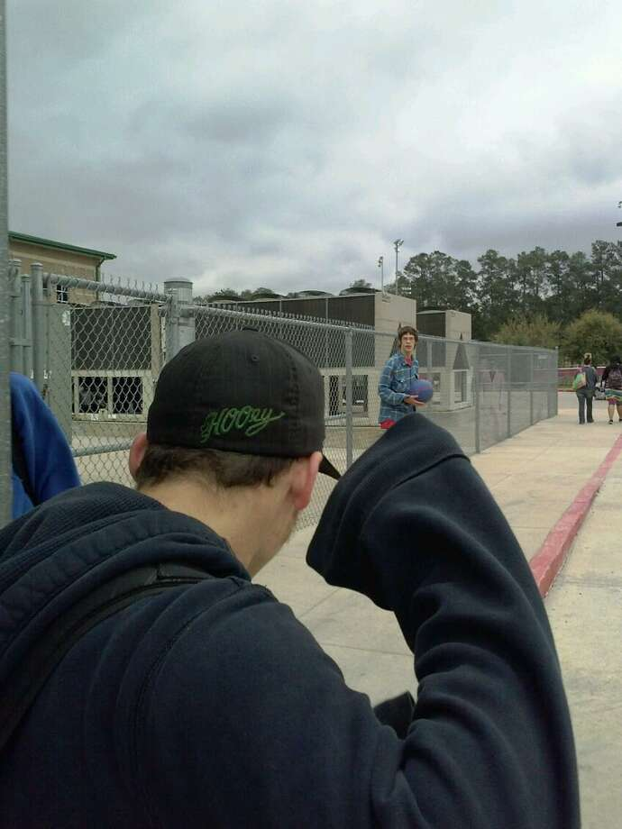 This cell phone photo taken April 15 by Marcella Davis at Cleveland High School depicts two ghostly figurures that were not present when the picture was taken -- a man in a suit by the chain-link fence and a woman slightly behind him. Photo: Courtesy Photo