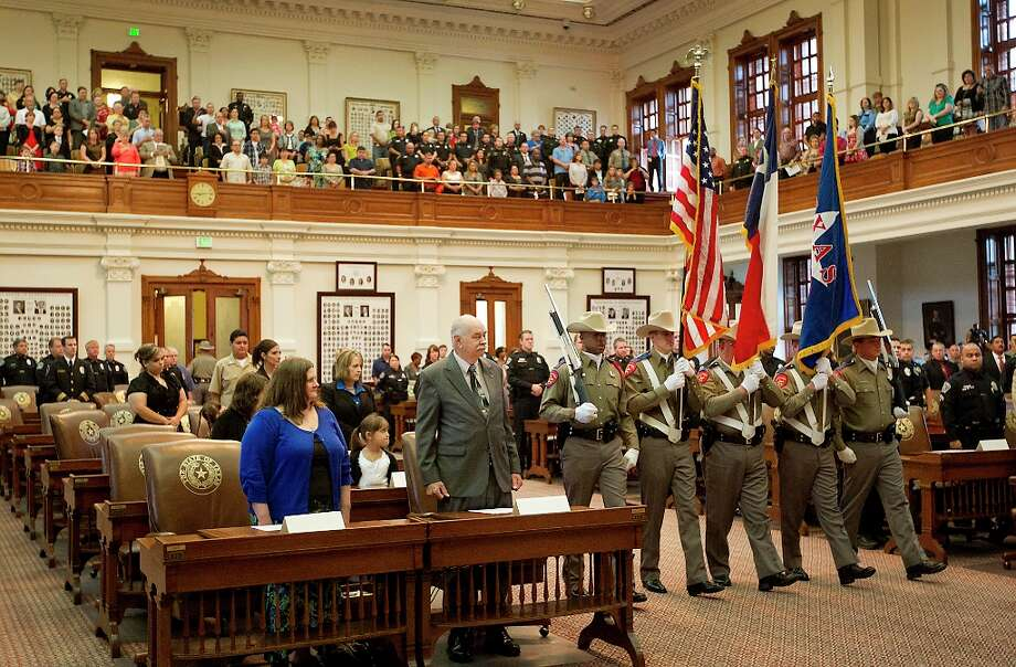 Attendees stands for the posting of the colors by the Texas Department of Public Safety honor guard, in Austin, Texas, Friday morning, Sept. 14, 2012. Texas Governor Rick Perry gave remarks and presented the 2012 Star of Texas Awards, which honor peace officers. firefighters, emergency medical first responders and federal law enforcement agents that have been seriously injured or killed inn the line of duty, during a ceremony in the House Chambers Friday morning.  (AP Photo/Statesman.com, Ralph Barrera)  MAGS OUT; NO SALES; INTERNET AND TV MUST CREDIT PHOTOGRAPHER AND STATESMAN.COM Photo: Ralph Barrera, Associated Press / American-Statesman