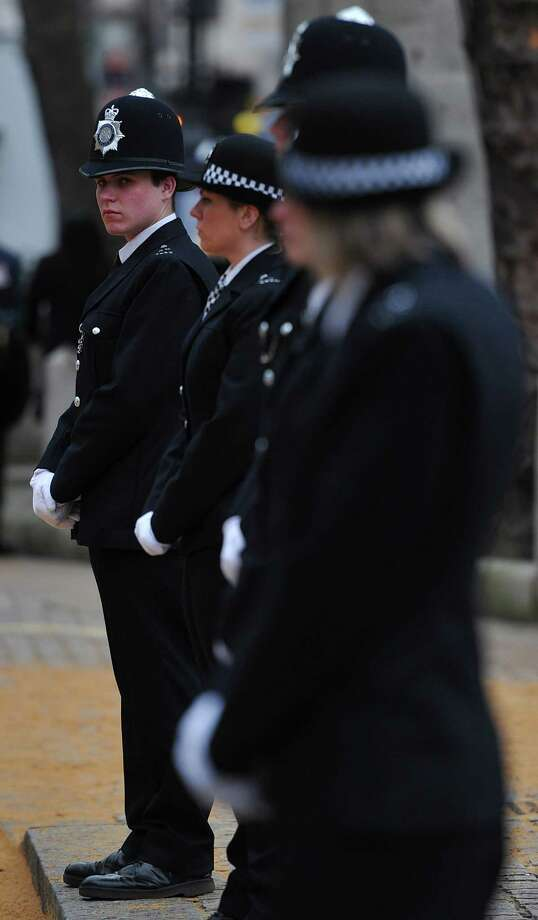 Police officers line the street ahead of the procession for the ceremonial funeral of British former prime minister Margaret Thatcher at the Church of St Clement Danes in central London on April 17, 2013. The funeral of Margaret Thatcher took place on April 17, with Queen Elizabeth II leading mourners from around the world in bidding farewell to one of Britain's most influential and divisive prime ministers.   AFP PHOTO / POOL / CARL COURTCARL COURT/AFP/Getty Images Photo: CARL COURT, AFP/Getty Images / AFP