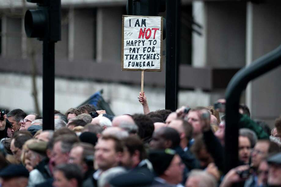 """TOPSHOTS A member of the crowd holds up a sign that reads """"I am not happy to pay for Thatcher's funeral"""" along he route of the procession during the ceremonial funeral of British former prime minister Margaret Thatcher in central London on April 17, 2013. The funeral of Margaret Thatcher took place on April 17, with Queen Elizabeth II leading mourners from around the world in bidding farewell to one of Britain's most influential and divisive prime ministers.  AFP PHOTO / POOL / CARL COURTCARL COURT/AFP/Getty Images Photo: CARL COURT, AFP/Getty Images / AFP"""